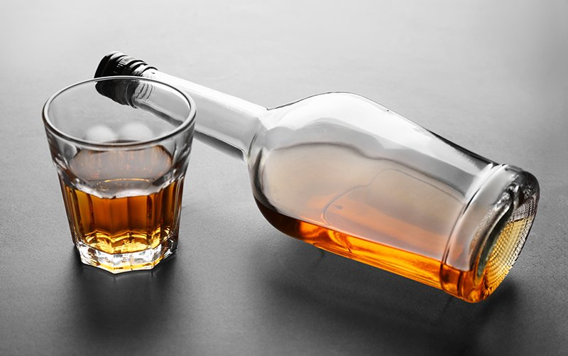 Alcoholism - A bottle of alcohol lays on its side next to a glass halk full of alcohol. Since alcohol in moderation is accepted in society those who battle alcoholism have an even harder time recovering.