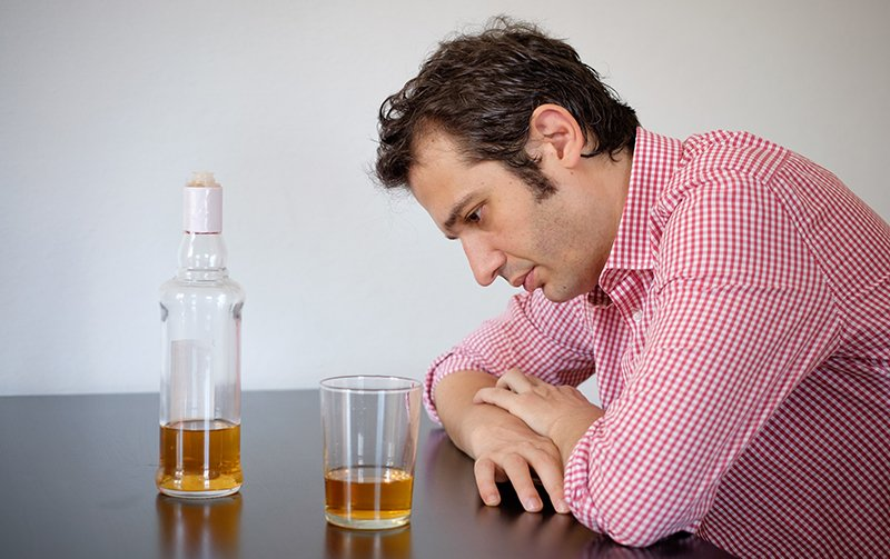 Alcoholism - A man sits at a table with his are folded on the table as he looks down with sadness. Since he has been laid off due to the Coronavirus lockdown his drinking has gotten out of control and he needs treatment for alcoholism.