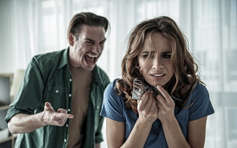 Drug Use - A man yells at a woman. Drug use and domestic violence often go hand in hand.