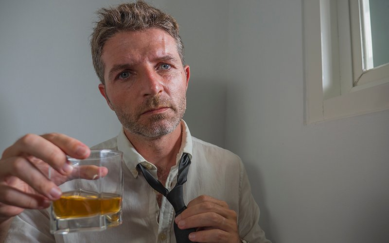 Substance Abuse in Lawyers - A middle aged man in a shirt and tie looks at the camera and holds up a glass of alcohol as he loosens his tie after a long day in court. The high stress legal industry leads to substance abuse in lawyers.