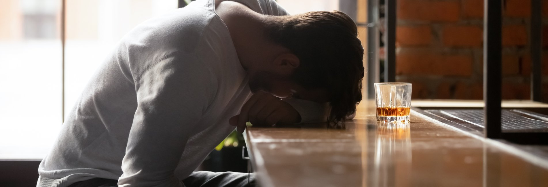 Generations and Addiction Resurgence - A depressed man struggling with alcohol addiction sits at a bar with his head down as he contemplates addiction treatment.