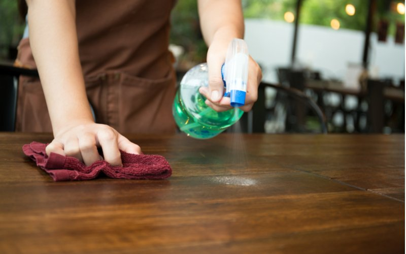 Hospitality Workers COVID-19 Addiction Resurgence - A hospitality worker is sanitizing a table at a restaurant that she works out to prevent the spread of germs and COVID-19