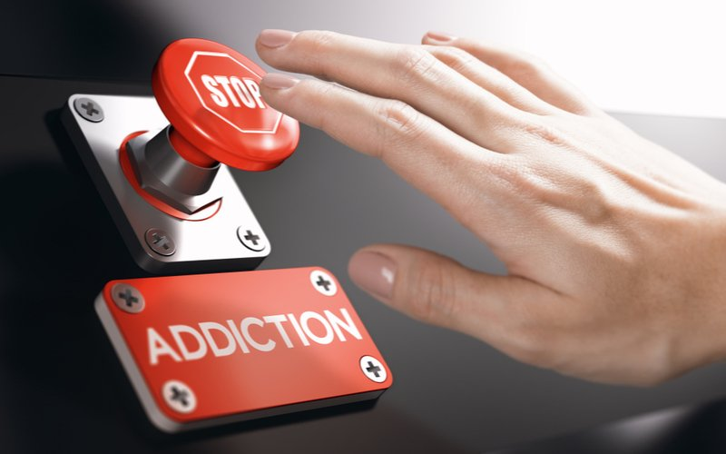 Addiction Prevention Campaigns and Mistakes Resurgence - A woman is pressing the Stop button on addiction because she is aware of prevention campaigns to prevent falling back into addiction, as well as potential mistakes to avoid so she does not relapse