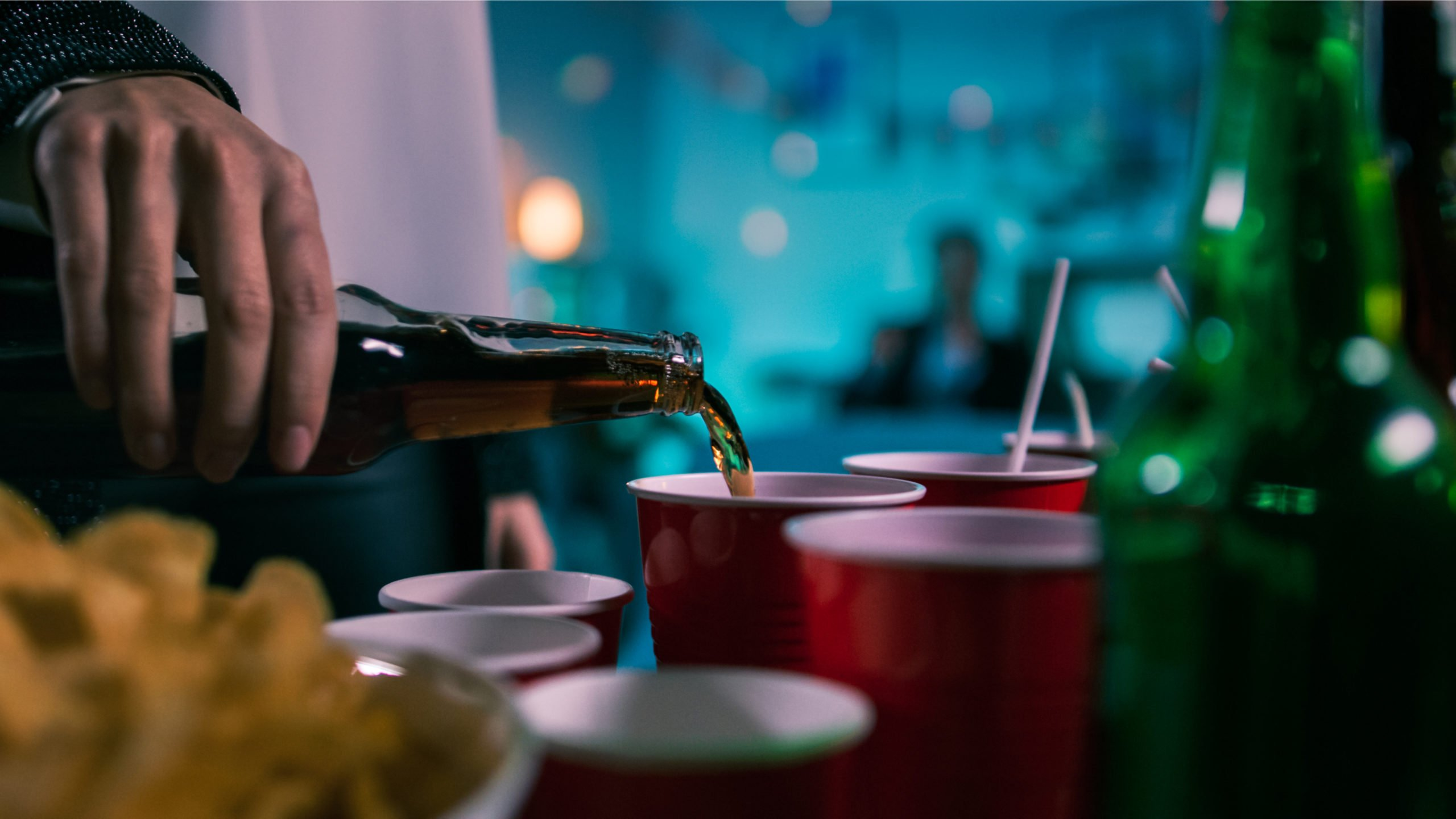 Most Commonly Abused Drugs in College Resurgence - A college student pours a beer into a cup during a drug and alcohol-infused party. If students use too much, drug rehab may be a good idea for them.