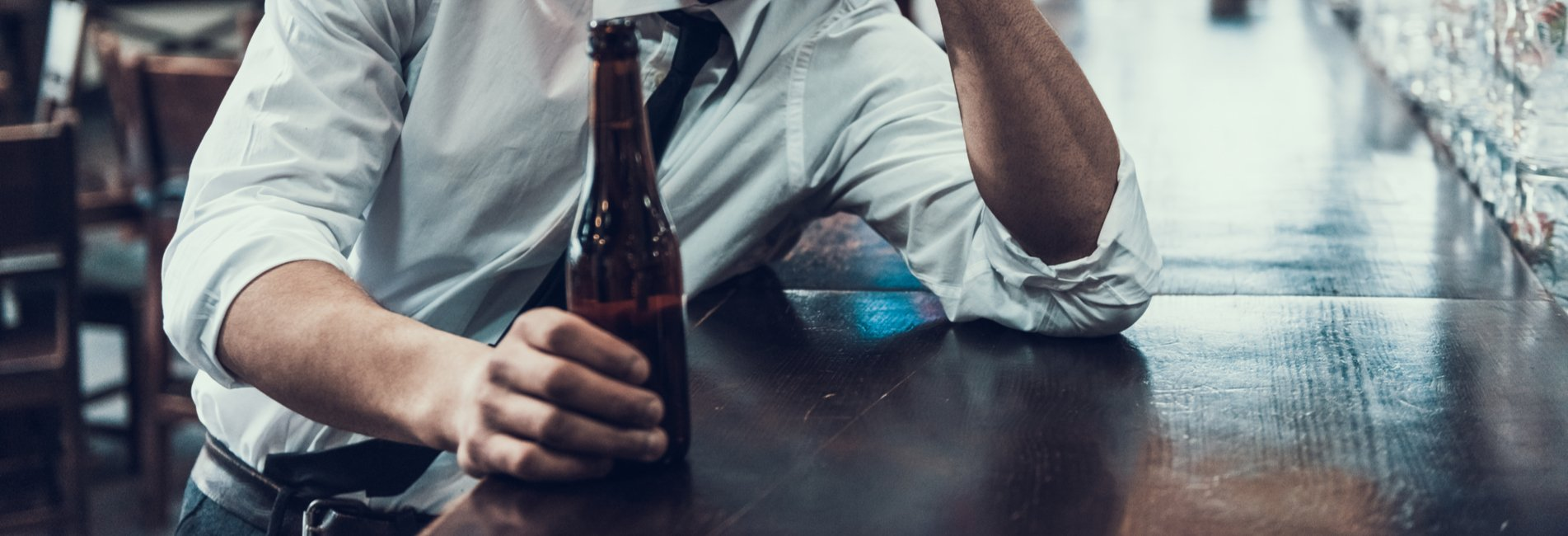 Why Alcohol is the Deadliest Drug Resurgence – A man with a beer at the bar. While he considers if he needs help getting sober, he should compare alcohol deaths vs other drugs and realize he needs help.