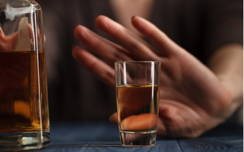 Reasons to Stay Sober in Difficult Times Resurgence - A woman is refusing a drink during a difficult time because it will only make things worse when you turn back to addictive behaviors during hard times