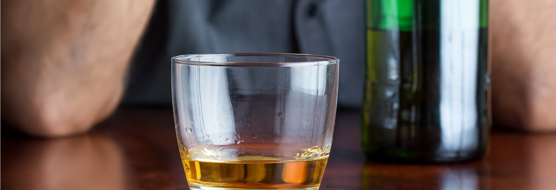 Blurred Lines Alcohol Abuse or Addiction Resurgence – A man with a bottle and glass of whiskey. It's important to understand the spectrum alcohol abuse falls along and get help when it's needed.