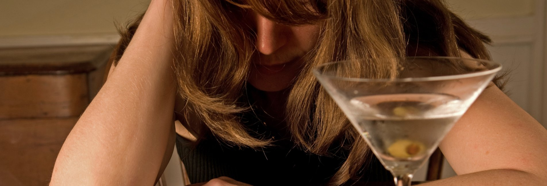 Letting Go of Bad Influences Resurgence – A woman cries with an alcoholic beverage in front of her. She should seek help for substance abuse in a treatment center.
