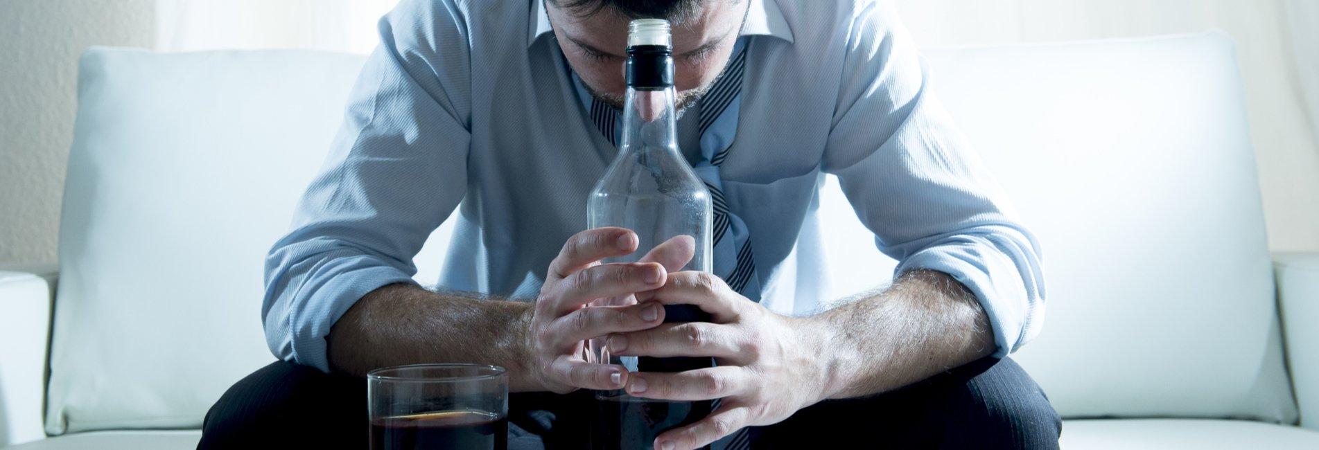 Stress and Addiction Resurgence – A man dealing with both stress and addiction holds a liquor bottle.