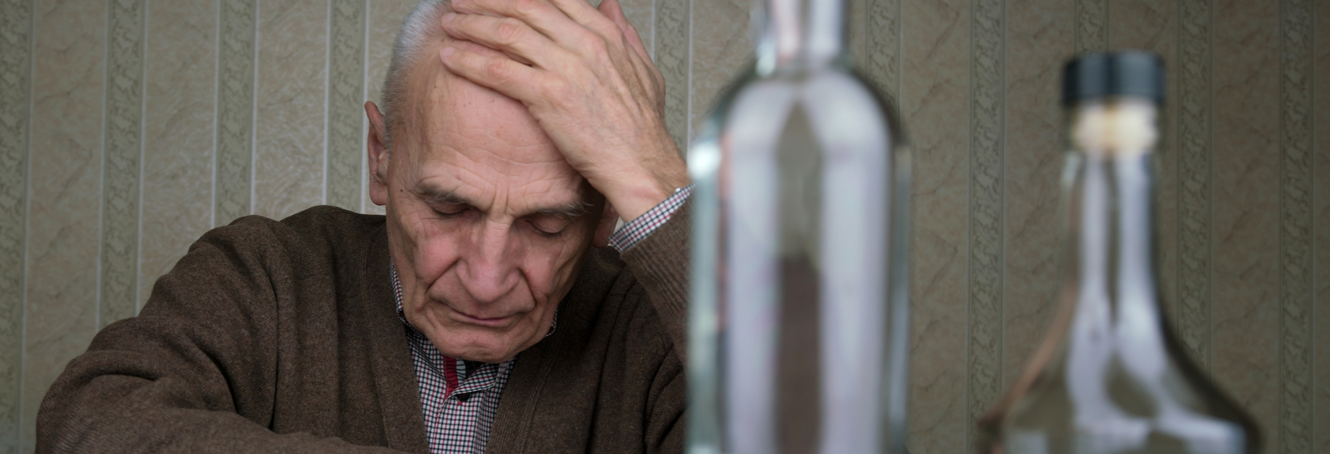 Addiction Treatment Steps for Those Struggling With Abuse - Resurgence - A depressed older man sits at his kitchen table with his hand to his head as he thinks about his need for addiction treatment steps to get clean from his alcohol abuse.