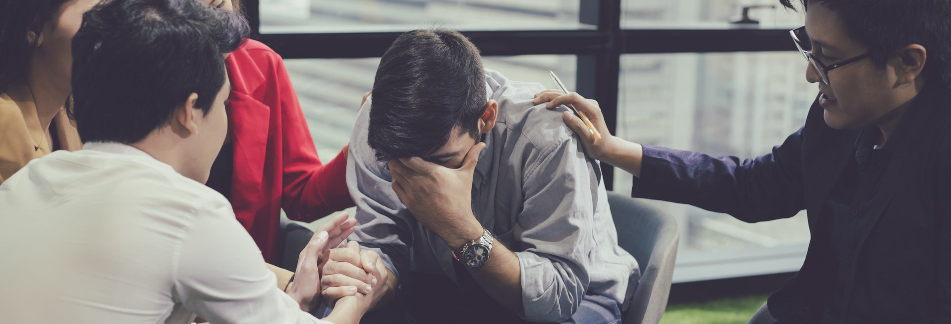Aftercare Plan For Substance Abuse and Addiction - Resurgence - Individuals attending an outpatient group therapy session are comforting another attendee in recovery as he puts his head in his hands and tears up trying to explain his frustrations with remaining sober.