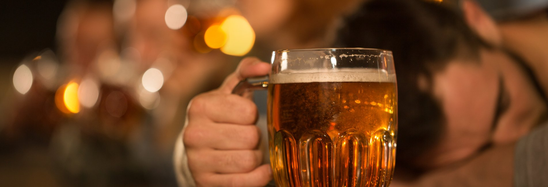 Alcohol and Blacking Out: How Are They Linked? Resurgence - A man is passed out at the bar with his head on the bar counter as he holds his beer mug, showing the dangerous link between alcohol and blacking out.