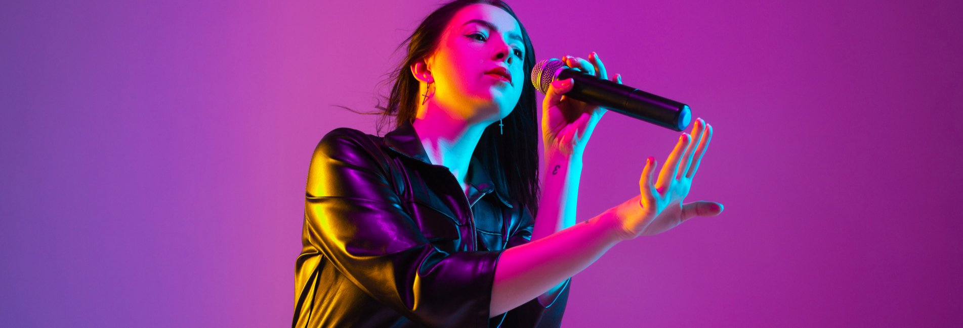Billboard's 100 Alcohol Lyrics in Music Resurgence - A young woman is singing into a microphone to symbolize the Billboard's Top 100 and the number of songs that contain alcohol lyrics in music.