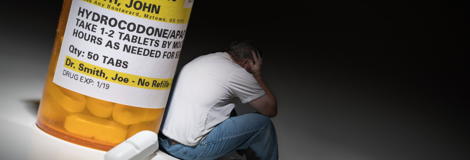Opioid Addiction and Our Nation Resurgence - A man is sitting next to a large bottle of Hydrocodone pills with his head in his hands because of his frustration with his opioid addiction.