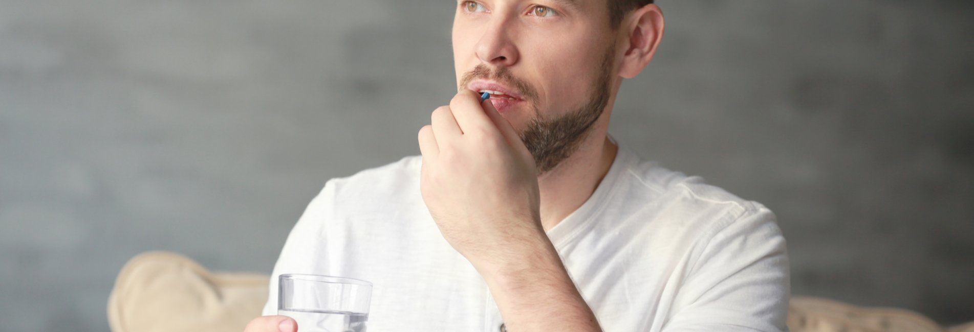 Valium Abuse and Treatment Resurgence - A young man takes another Valium in the morning with a glass of water while staring faintly in the distance knowing that he is engaging in Valium abuse and may need to seek professional treatment.