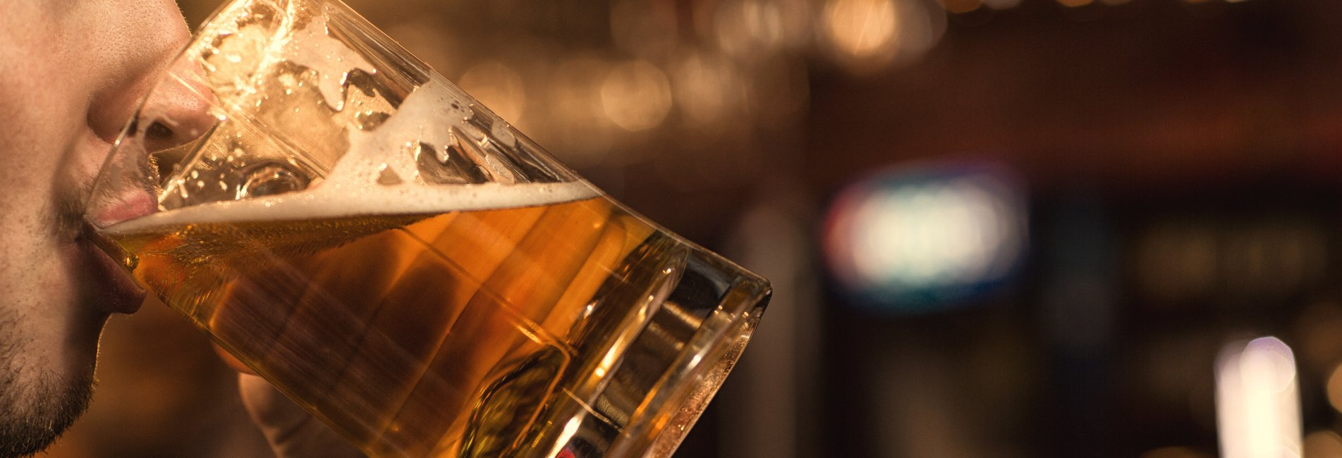 Alcohol Abuse - Resurgence - A man is sitting at a bar and partaking in alcohol abuse as he binge drinks another beer at a bar.