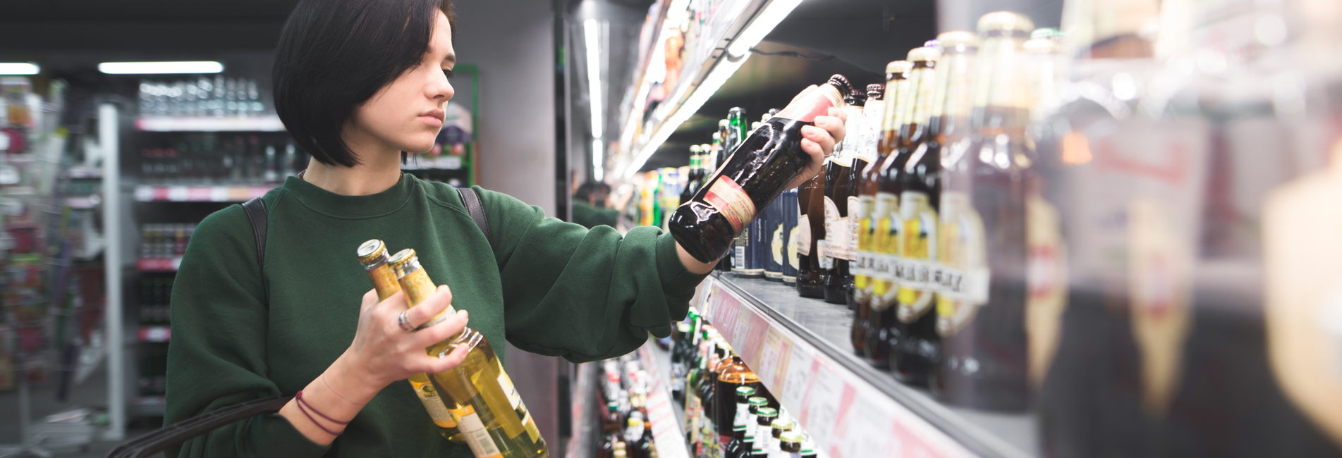 Alcohol Rehab Centers in Costa Mesa CA - Get Help Today - Resurgence - A woman is in a store trying to avoid purchasing alcohol, but she cannot help it and needs to attend one of the leading alcohol rehab centers in Costa Mesa CA.