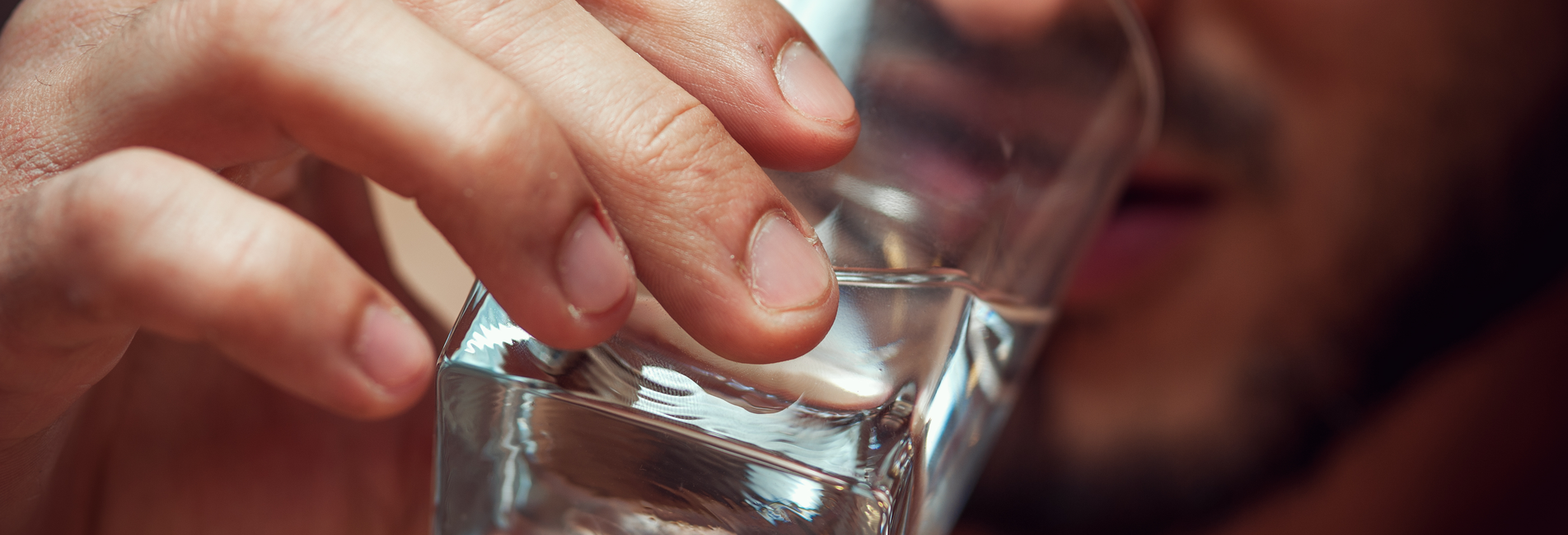 Alcohol Treatment in California - Get Addiction Help Now - Resurgence - A man chugs a glass of hard liquor as he contemplates getting alcohol treatment in California.