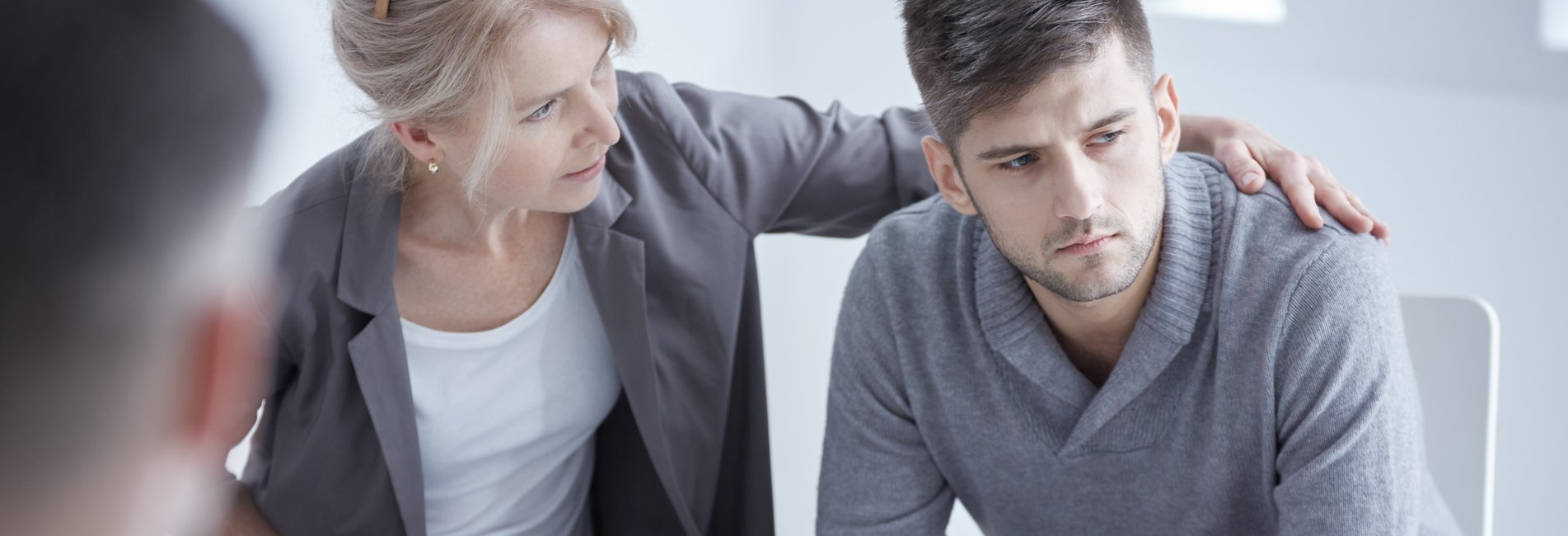 Online Addiction Treatment - Resurgence - A young man is comforted by his mother and addiction therapist during a family therapy session for his online addiction treatment.